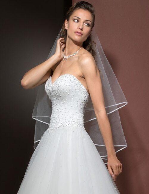 Den smukke stropløse top på denne brudekjole har masser af perler. Prøv kjolen hos Unique Kjoler.