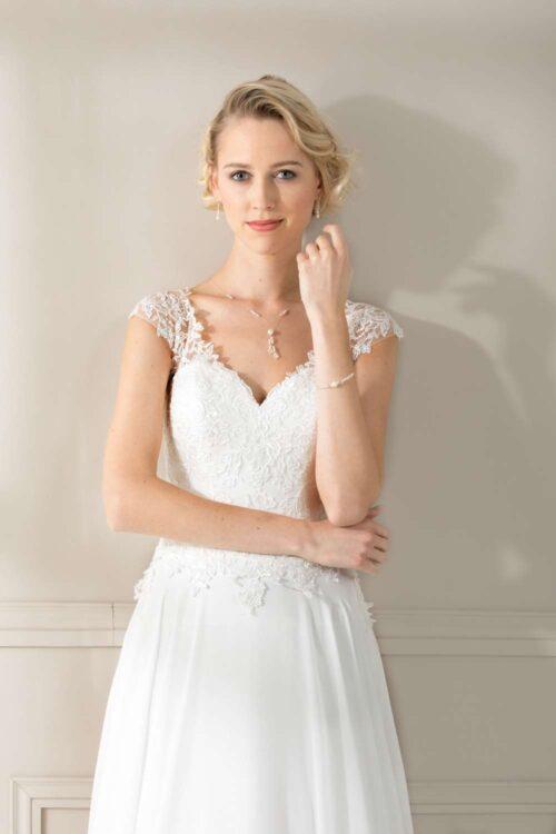 Super feminin brudekjole med blonder, v-udskæring for og bag samt elegant slæb.