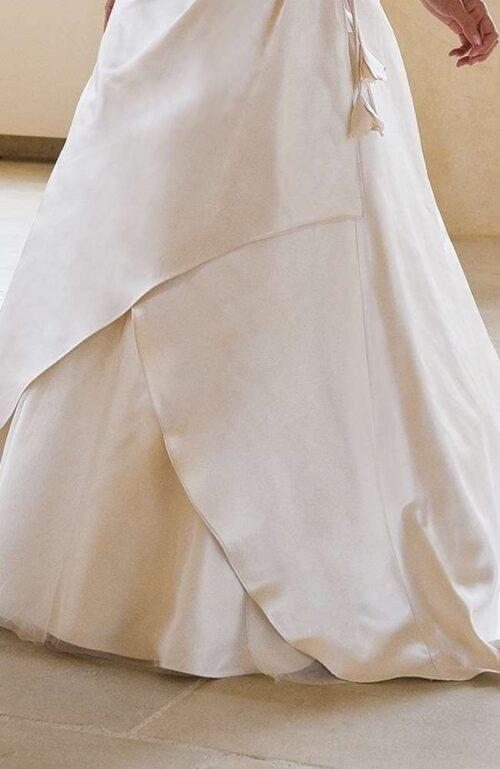 Brudekjolen Fina fra Unique Kjoler er i blødt satin med slæb og flotte draperinger.