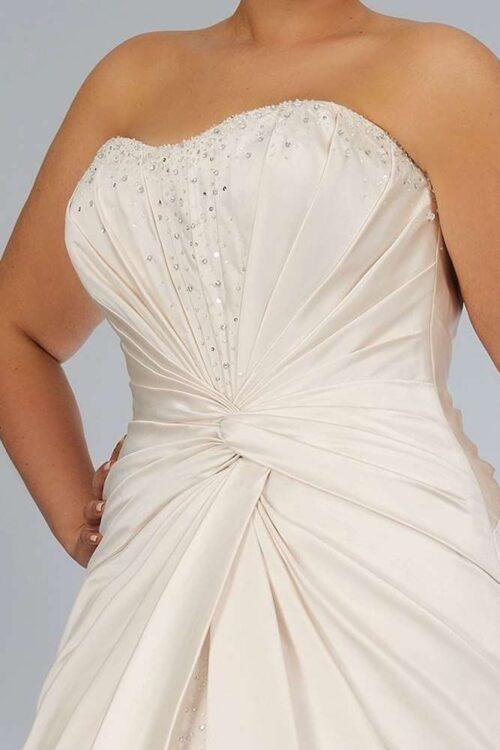 Flotte draperinger og perler pryder denne smukke plus size brudekjole fra Unique Kjoler.